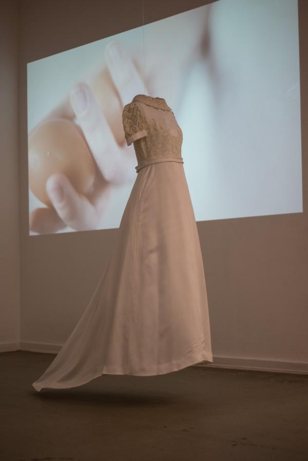 """N.N. 2013. Das Brautkleid meiner Mutter. Dahinter läuft die Videoarbeit """"what will be"""""""